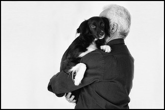 Man holding small black and white dog